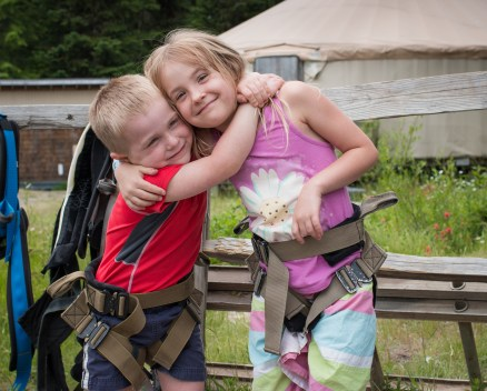 brother and sister hugging before rock wall