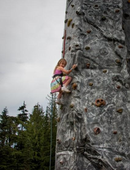 little girl climbing rock wall