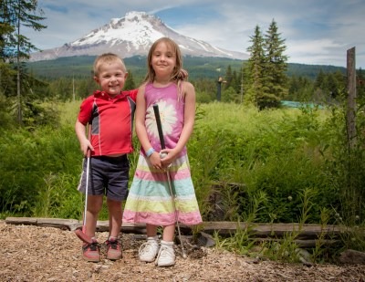 little brother and sister posing in front of mount hood