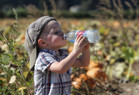 little boy drinking water on a hot day