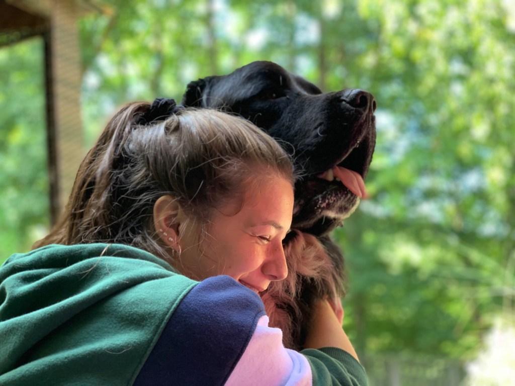 girl hugging newfoundland dog