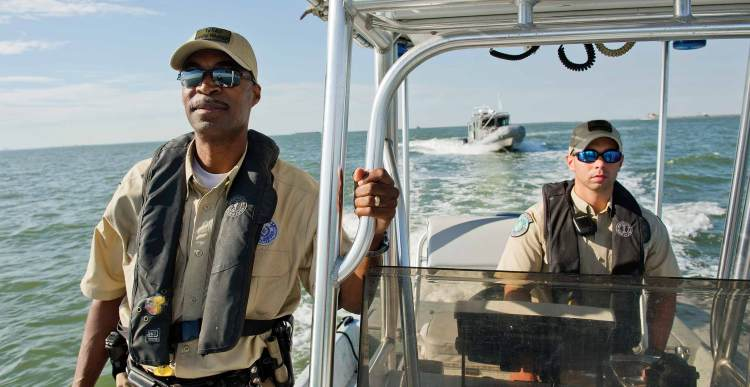 Texas Parks and Wildlife officials on boat in lake