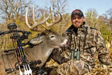 Bow hunter with white tail buck.
