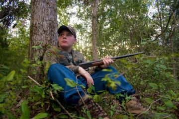 Young hunter holding gun.