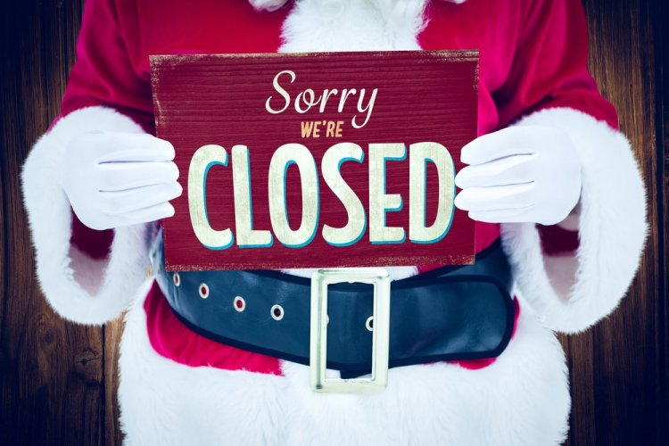 Santa holding sign that says 'closed.'