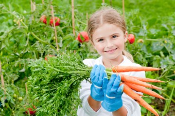 girl in garden holding carrots