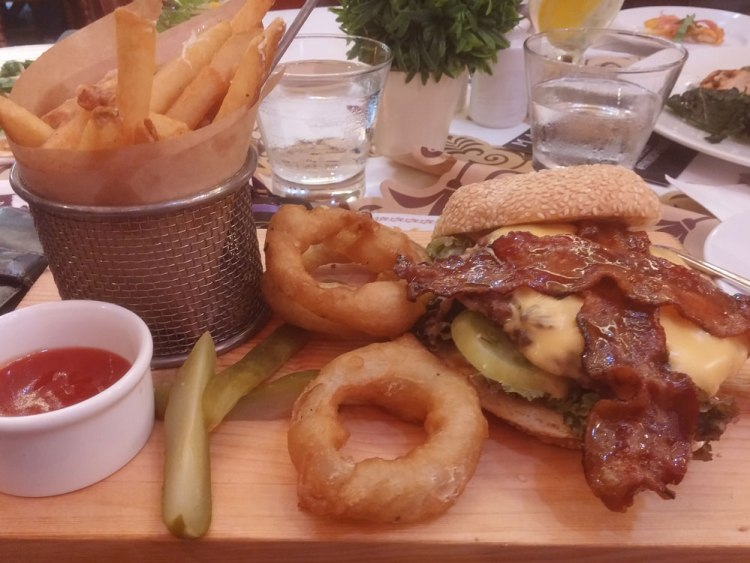The Maple Burger is juicy grilled beef patty that comes with American cheese, lettuce, pickles, tomatoes, onion rings, and maple-glazed bacon.