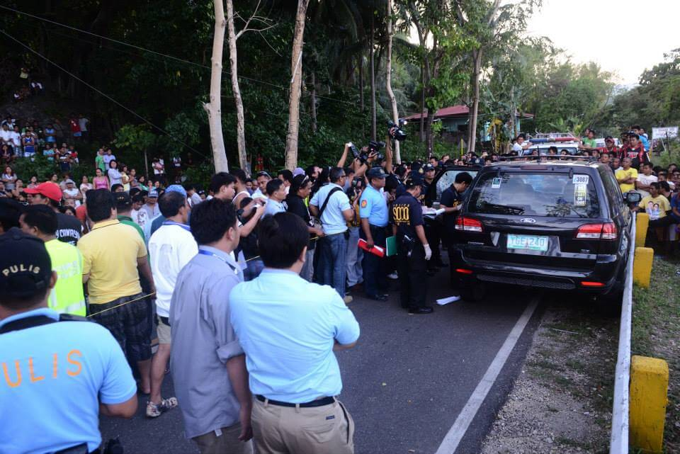 Police go over the vehicle lawyer Noel Archival was riding when he was ambushed and killed in Dalaguete. (Photo by Mark Luzano)