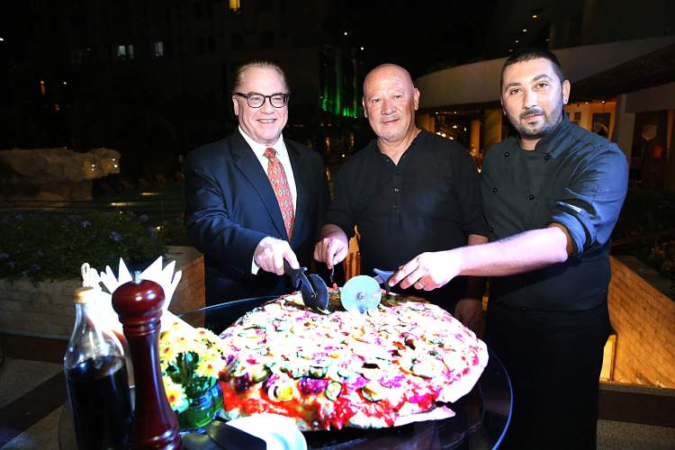 PIZZA SLICING CEREMONY. Opening La Dolce Vita with a pizza-slicing ceremony are (from left) Marco Polo Plaza General Manager Brian Connelly and guest chefs Giuseppe Genco and Luca Genco.