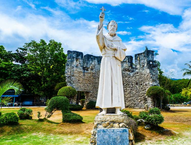 EL PADRE CAPITAN. The statue of Fr. Julian Bermejo OSA in Oslob stands in front of the ruins of the baluarte – the watchtower part of a network that he organized to protect southern Cebu towns from Moro raiders.