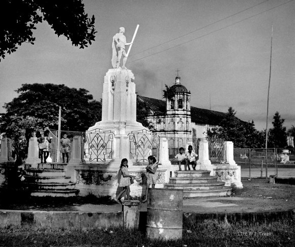 "LAPULAPU. A photograph of the Lapulapu stature on October 10, 1949 by ""Life"" photographer Jack Birns. Beyond the statue is the old Opon church. (Photo from John Tewell's Flickr account)"