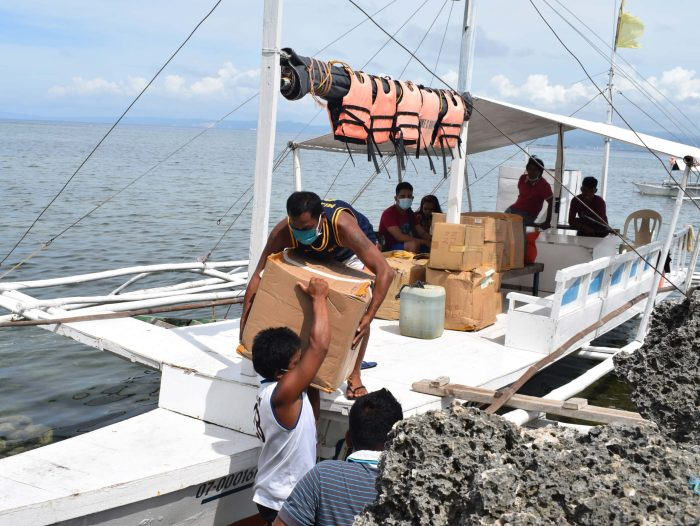 Unloading of the boxes from the boat on the way to Gilutongan Integrated School.