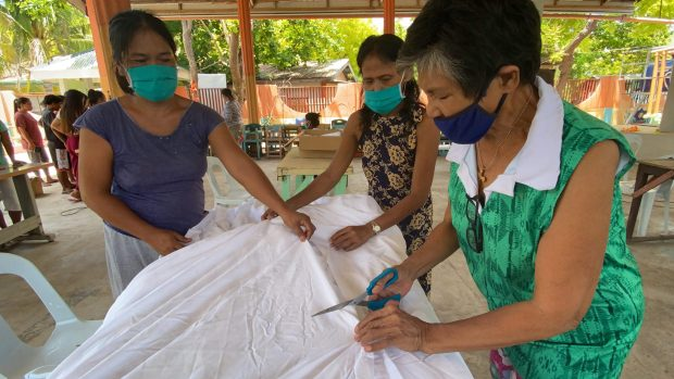 Volunteers portioning the linen to start sewing the face masks.