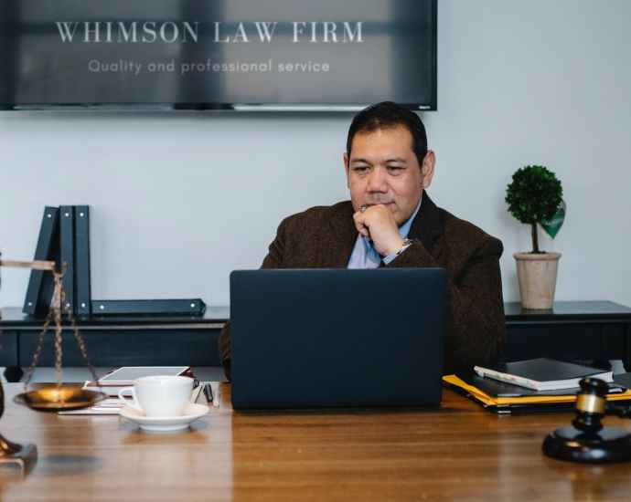 asian lawyer working with laptop near scales of justice