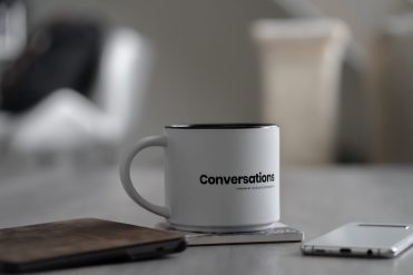 Joyology 101: Listening with Patience white conversations printed mug near smartphone