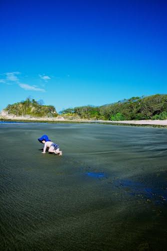 child crawling away on beach