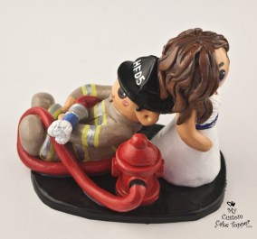 Bride dragging her fireman groom cake topper
