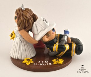 Bride dragging her fireman groom wedding cake topper