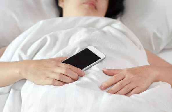 women in bed with cell phone