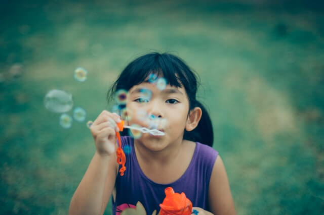 girl blowing bubbles parenting humour