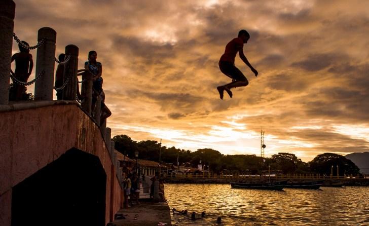 夕方に橋の上から川の中に飛び込む少年