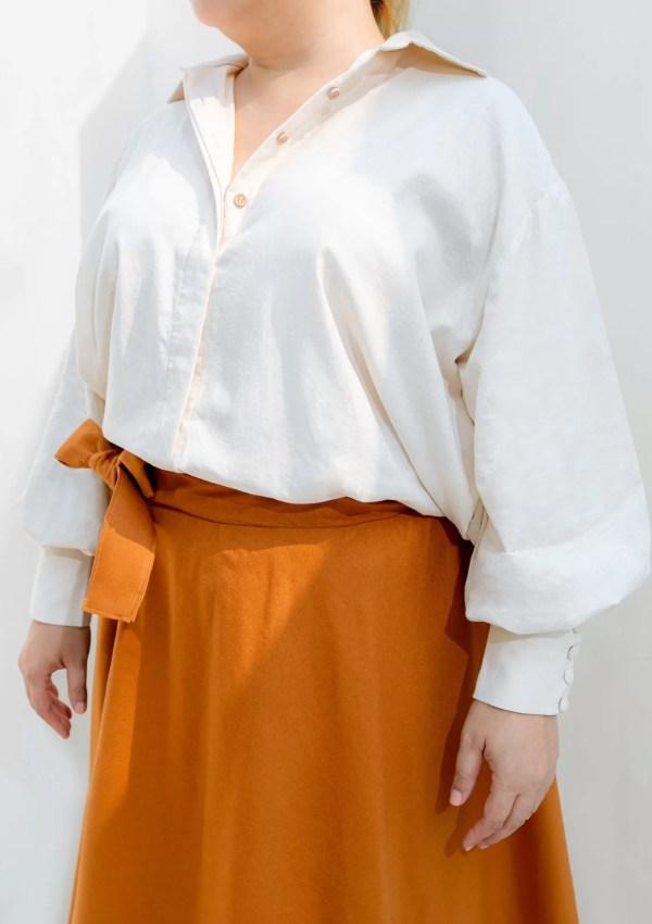 Plus size woman wearing orange cotton skirt and beige shirt