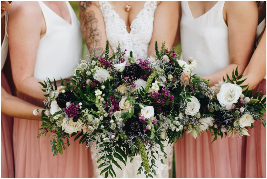 Bride with her bridesmaids holding loose wild-flowered bouquet by Keleidoscope Custom Florals + Butterbee Farm. |Eastern Shore Wedding|