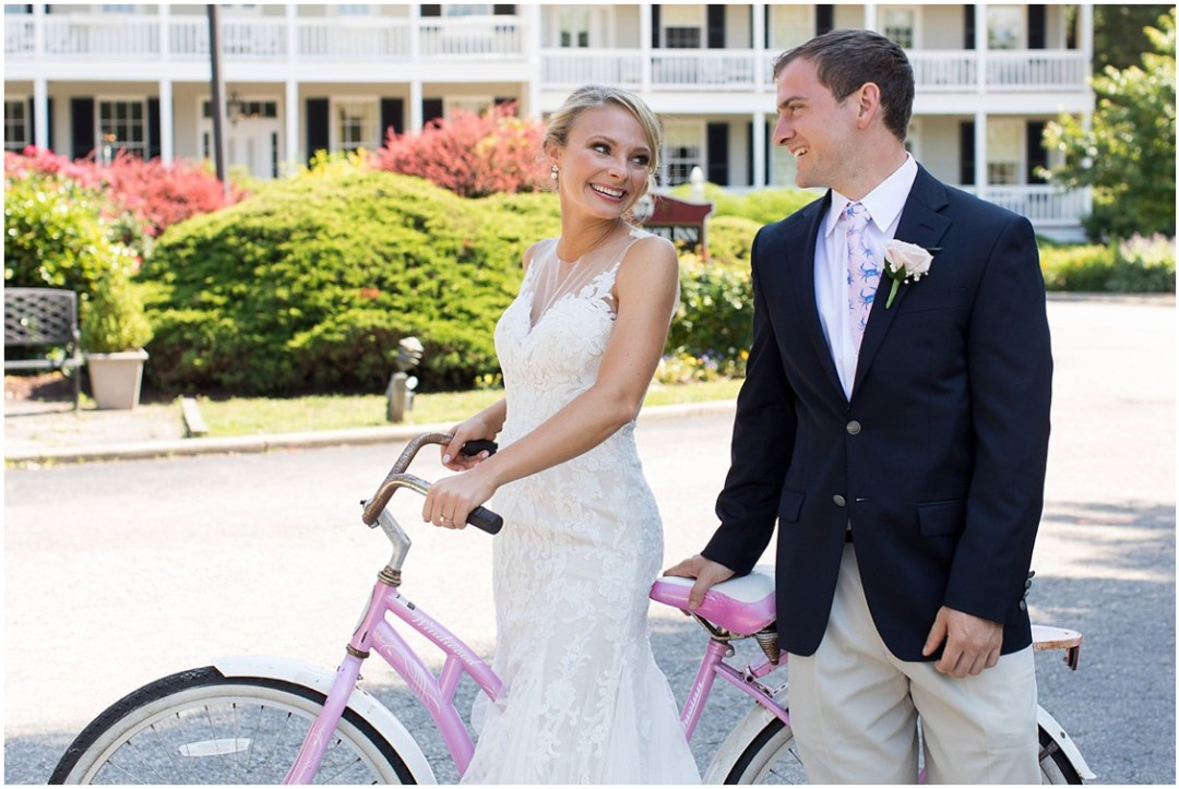 Bride and groom standing by pink and white bicycle together. | My Eastern Shore Wedding |