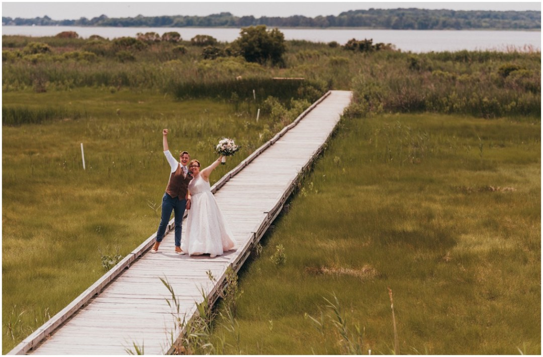 Married couple on long wooden dock with arms raised. | My Eastern Shore Wedding |