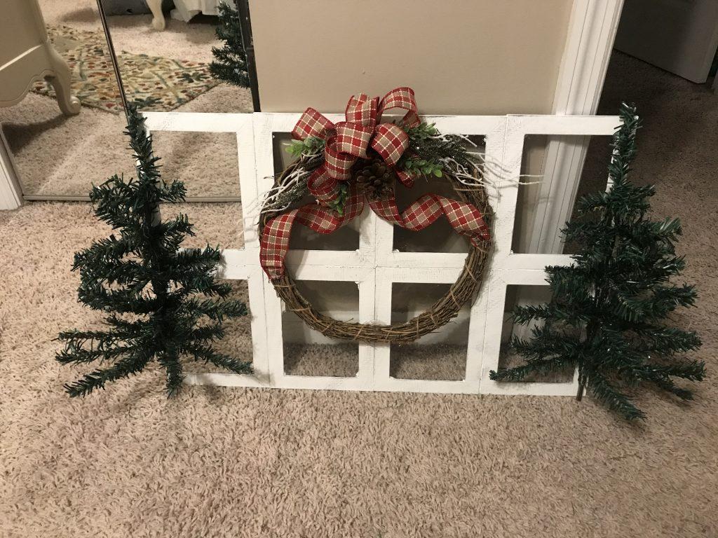 adding a Christmas wreath to farmhouse window