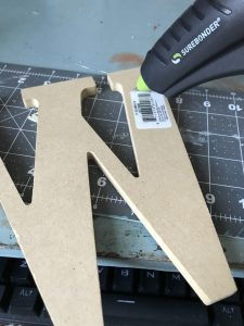 putting hot glue onto wooden letter