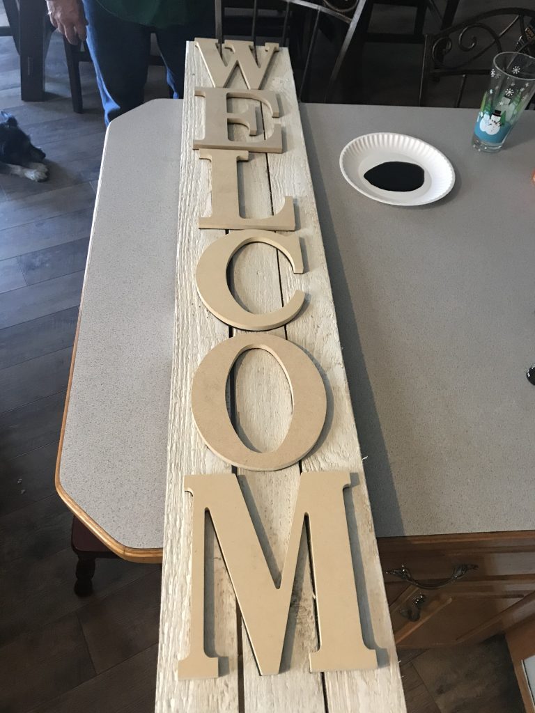 wooden letter stamps centered on pallet wood porch sign