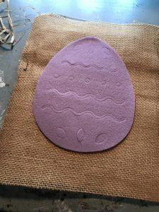felt egg cutout on top of burlap fabric