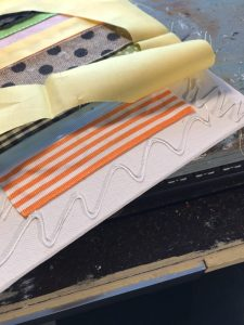 gluing solid fabric onto canvas around ribbon easter egg