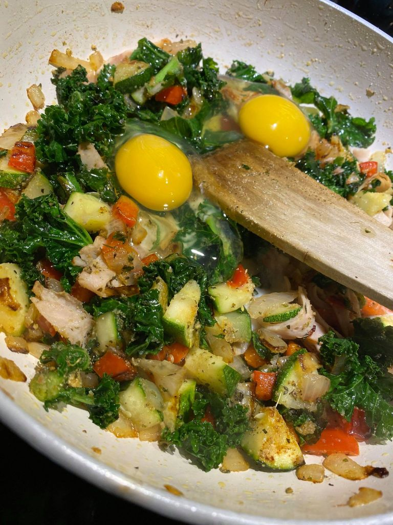 eggs being added to pan of vegetables