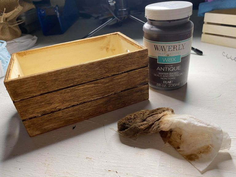 Dollar tree crate being stained using Waverly antique wax