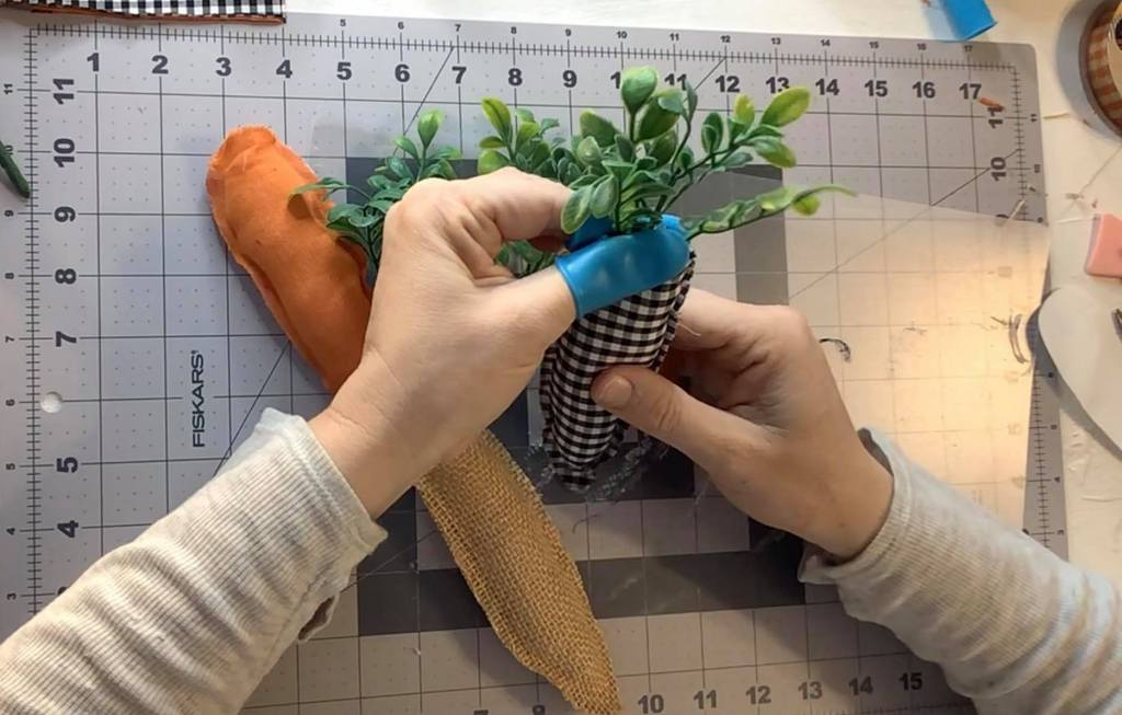 adding greenery to fabric carrots | farmhouse spring carrot garland | carrot decorations | farmhouse Easter decor | ideas for a spring mantel | Easter mantel ideas | spring mantel decor ideas | #eastermantel #carrotgarland