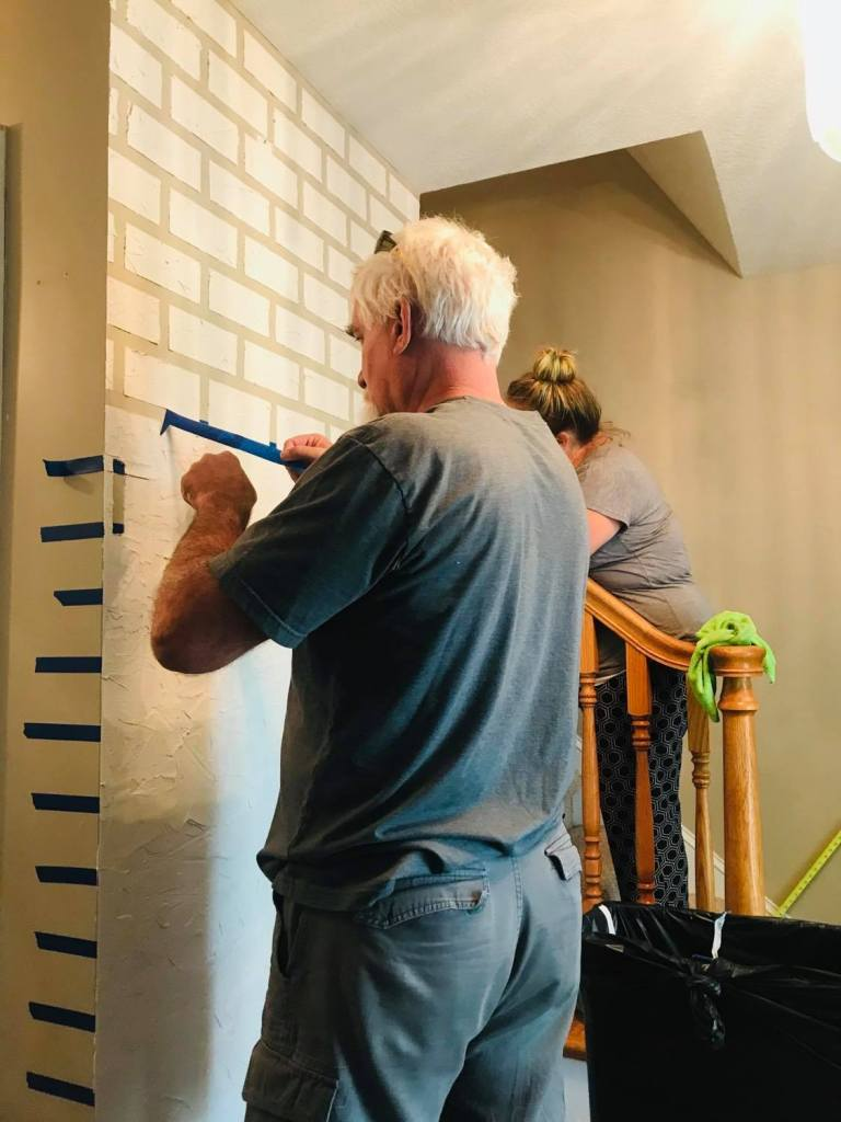Removing painters tape from wall for faux brick design | #fauxbrickwall