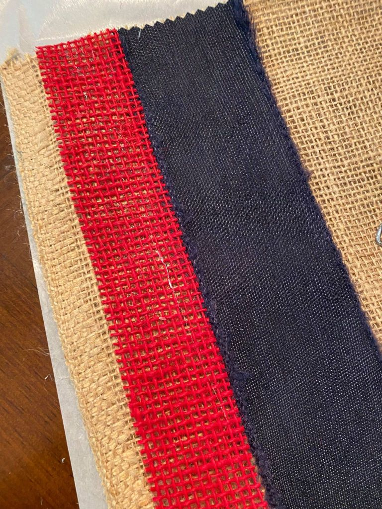 adding red burlap ribbon to the edge of a burlap table runner
