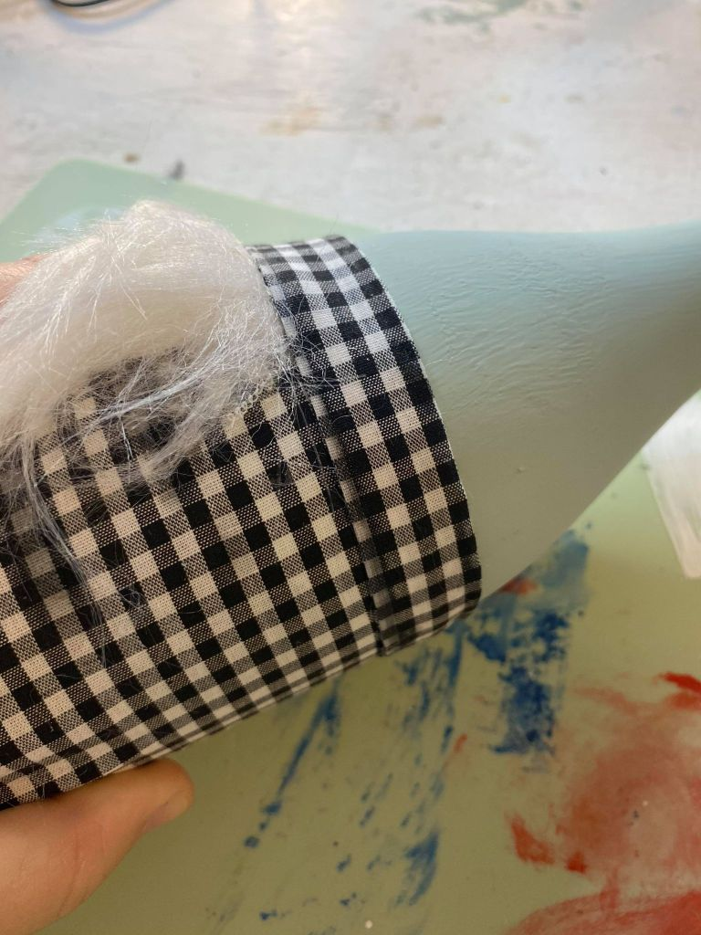 adding a hemmed edge around the raw edge of fur on a gnome made out of a wine bottle
