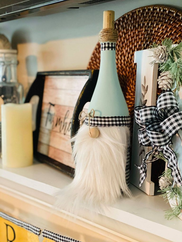 farmhouse gnome made out of a wine bottle sitting on a farmhouse mantel