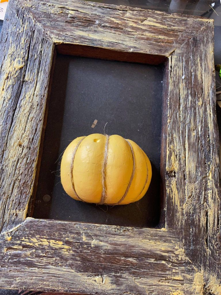 split pumpkin added to a rustic frame for a fall DIY