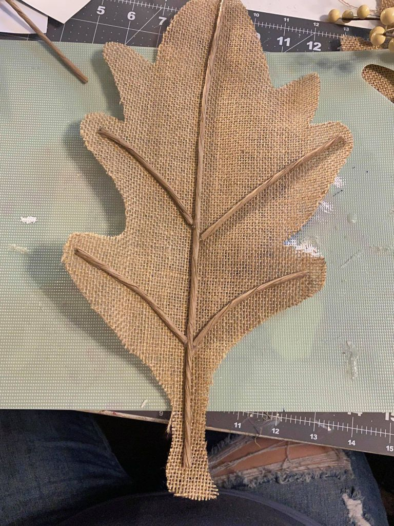 adding paper stem wire to a burlap leaf to make the ribs of the leaf