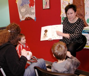 Lisa Nakamura of the Edmonds Center for the Arts reads to children at Revelation's Yogurt Saturday.