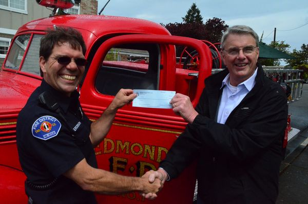 "Greg Jorgenson of the Edmonds Museum Board presented a $1000 check to Edmonds firefighter Dave ""Bronco"" Erickson to help complete the Fallen Firefighter Memorial in front of the Edmonds Fire Station. ""The money will help with the cost of installing a girder salvaged from the wreckage of the Twin Towers after the 9-11 attacks,"" said Erickson. ""This piece of our history memorializes our brother and sister firefighters who lost their lives that day."" The money was raised through sales of raffle tickets for a classic child's pedal fire truck.  The Museum will raffle off another this year."