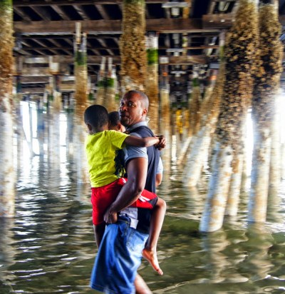 A dad wades through water while carrying his two sons.