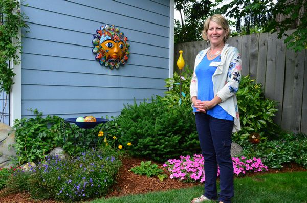 "Sam Christensen proudly stands in a corner of her garden, stop No. 5 on this year's self-guided tour. ""My husband Paul and I bought this place in 2005,"" she said. ""Gardening is my passion, and we're so happy to have transformed it into a garden retreat."""