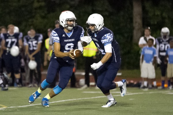 Meadowdale quarterback JP Routen hands off to Spillum.