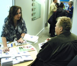 Community Resource Advocate Nancy Budd answers questions from an open house visitor.
