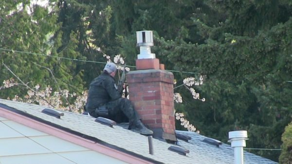A SWAT team sniper waits on the roof next to the house where the suspected car thief took refuge before surrendering to police April 9. (Photo by Larry Vogel)